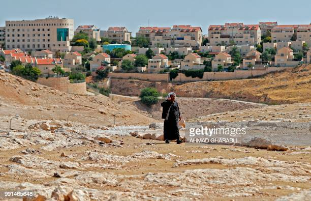 A man walks in the Bedouin village of Abu Nuwar east of Jerusalem in the occupied West Bank with the Israeli settlement of Maale Adumim in the...