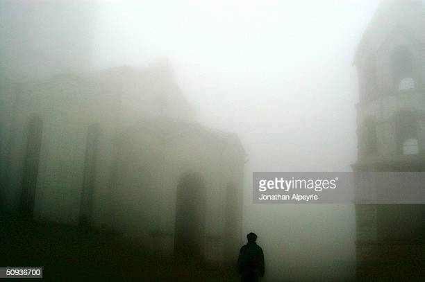 Man walks in the early morning fog at the Shushi Cathedral April 26, 2004 in Nagorno-Karabakh, Azerbaijan. During the war, the cathedral was badly...