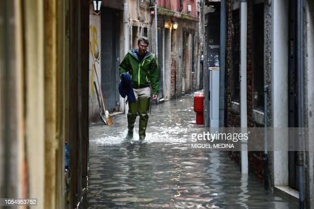 A man walks in the flooded street near Rialto Bridge during a acquaalta alert in Venice on October 29 2018 The flooding caused by a convergence of...