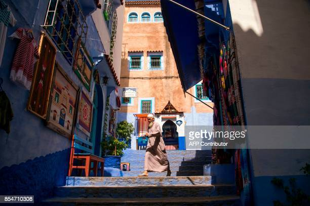 A man walks in the Medina of the northwestern Moroccan city of Chefchouen in the northern Rif region on September 21 2017 Huddling against a hillside...