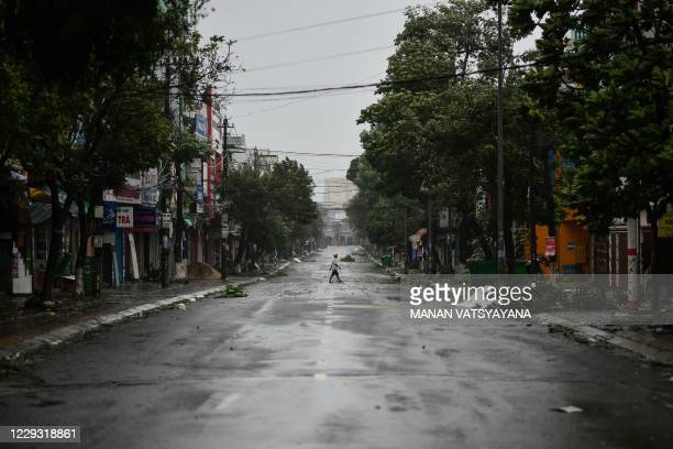 Man walks in the middle of a deserted road amid strong winds in central Vietnam's Quang Ngai province on October 28 as Typhoon Molave makes landfall.