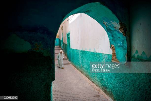 TOPSHOT A man walks in the northern Moroccan town of Moulay Driss Zerhoun on July 26 2018 Each summer tens of thousands of people flood the small...