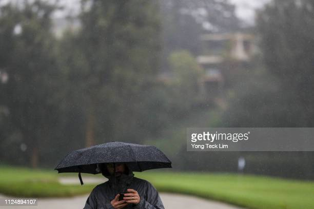 Man walks in the rain as play is suspended during the first round of the Genesis Open at Riviera Country Club on February 14, 2019 in Pacific...
