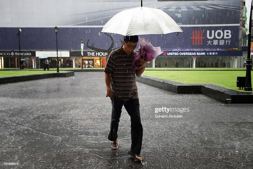 A man walks in the rain with a bouquet of flowers in hand during Valentine's Day at Raffles Place on 14 February, 2013 in Singapore. Valentine's Day is a time to celebrate love, romance and friendship and is celebrated worldwide annually in different ways on February 14.