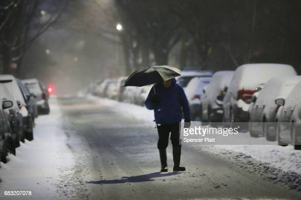 A man walks in the sleet and snow on March 14 2017 in New York City New York City and New Jersey are under a state of emergency as a blizzard is...