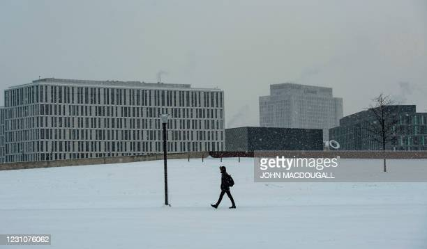 Man walks in the snow in Berlin's so-called government district, with the Charite hospital seen in the background, on February 10, 2021.