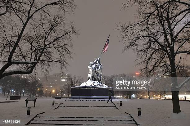 A man walks in the snow in front of the Iwo Jima memorial in Washington DC on February 16 2015 The eastern United States braced for an arctic...