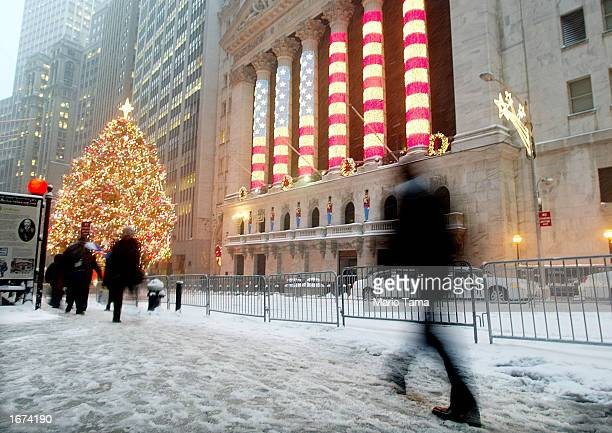 Man walks in the snow in front of the New York Stock Exchange Christmas tree and holiday flag display December 5, 2002 in New York City. The city is...