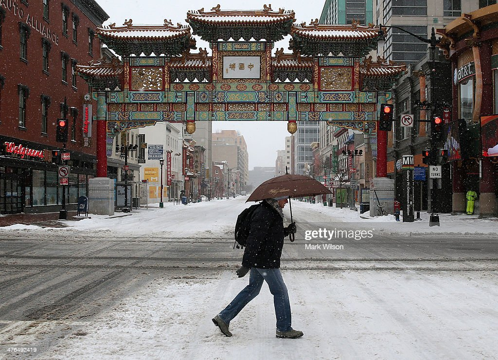 A man walks in the snow near the China Town arch on March 3, 2014 in Washington, DC. The Federal Governent is closed due to major snow storm that is expected to dump up to 8' of snow in the Washington area.