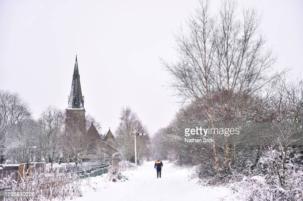 Man walks in the snow past Silverdale Church on December 29, 2020 in Newcastle-Under-Lyme, England. Heavy snow fall has covered the West Midlands as...
