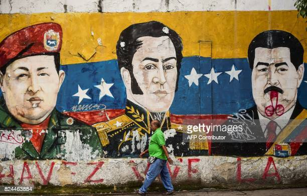TOPSHOT A man walks in the street during elections for a Constituent Assembly in Caracas on July 30 2017 Polls opened in Venezuela on Sunday for the...