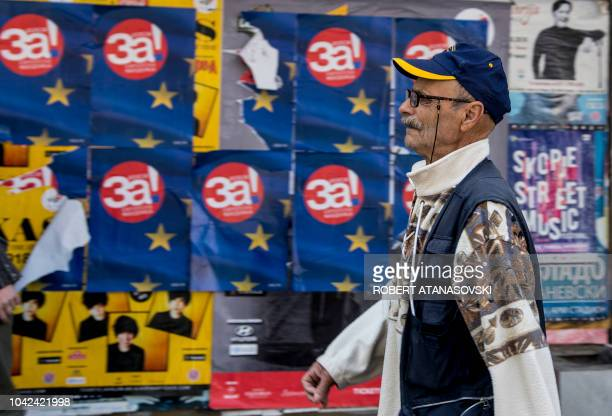 TOPSHOT A man walks in the street past posters reading Yes for European Macedonia in Skopje on September 28 2018 Voters across the Balkan state of...