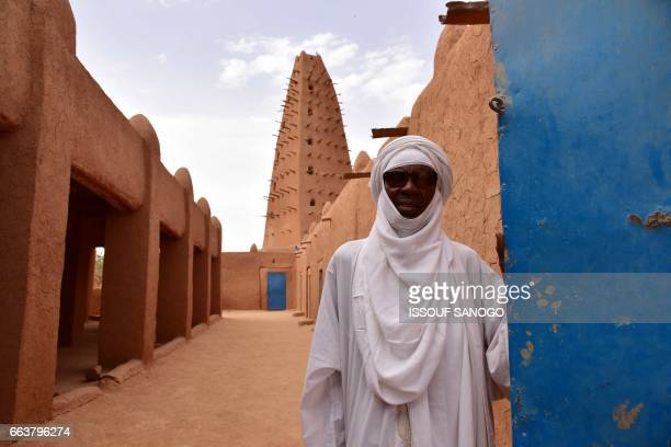 A man walks in the vicinity of a earthen mud mosque in Agadez in northern Niger on April 2 2017 / AFP PHOTO / ISSOUF SANOGO