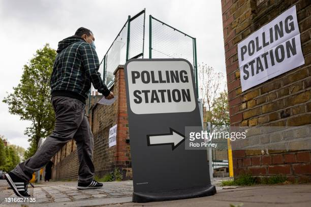 Man walks into a polling station at Walnut Tree Walk Primary School on May 06, 2021 in London, England. The London mayoral election takes place today...