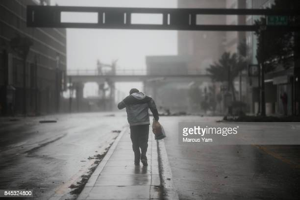 A man walks into the wind as the passing Hurricane Irma brings wind and rain to downtown Miami Fla on Sept 10 2017