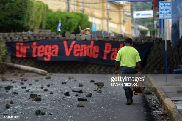 TOPSHOT A man walks near a barricade with a banner reading Ortega Nation Seller referring to Nicaraguan President Daniel Ortega at Monimbo...