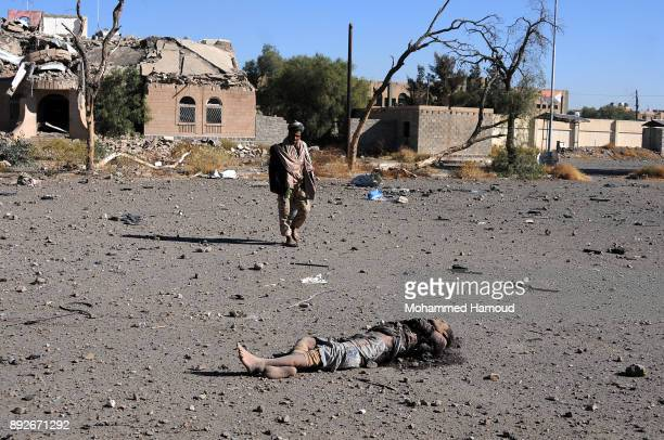A man walks near a body of a prisoner after he was killed in airstrikes targeted the prison on December 13 2017 in Sana'a Yemen More than 12...
