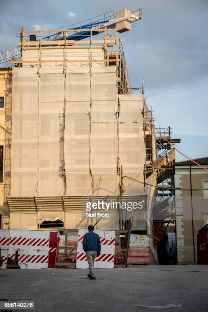 Man walks near a damaged building in historic center of L'Aquila, on March 21, 2017. The Eighth anniversary of the L'Aquila earthquake will be marked...