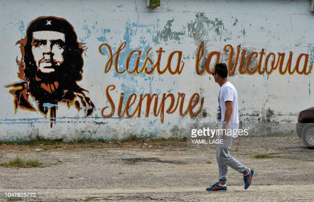 A man walks near a graffiti depicting Argentineborn revolutionary leader Ernesto Che Guevara in Havana ahead of the 51st anniversary of his death on...