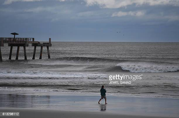 Man walks near a pier, part of which washed out in the sea, in Jacksonville Beach, Florida, on October 8 after Hurricane Matthew passed the area. A...
