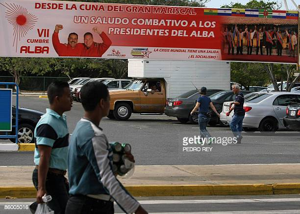 A man walks near a sign announcing the VII Bolivarian Alternative for the Americas Summit at the exit of the Gran Mariscal Antonio Jose de Sucre...