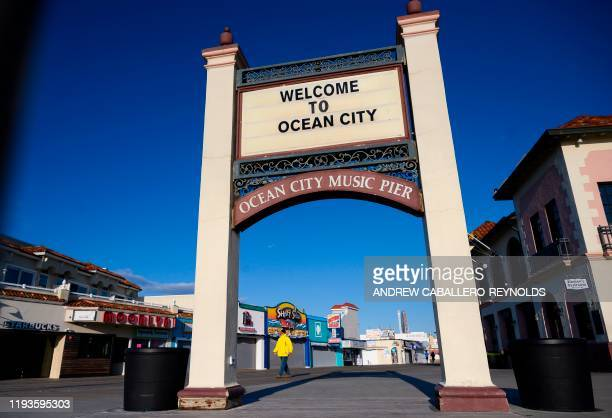 Man walks near a sign on the Ocean City music pier in Ocean City, New Jersey on January 8, 2020. - Pizza joints and popcorn stands jostle for...