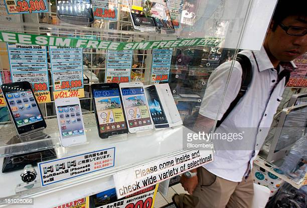 A man walks near Apple Inc iPhones left and Samsung Electronics Co Galaxy smartphones displayed at an electronics store in Tokyo Japan on Tuesday Aug...