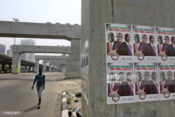 A man walks near campaign posters of Atiku Abubakar candidate of the main opposition People's Democratic Party under mono rail line pillars under...