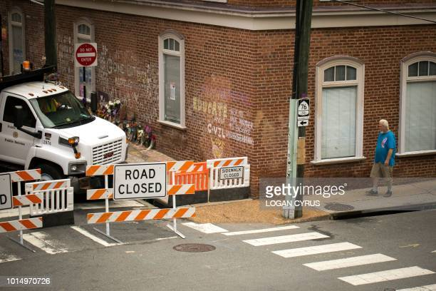 TOPSHOT A man walks near closed road signs at the makeshift memorial for Heather Heyer in Charlottesville Virginia on August 11 on the year...