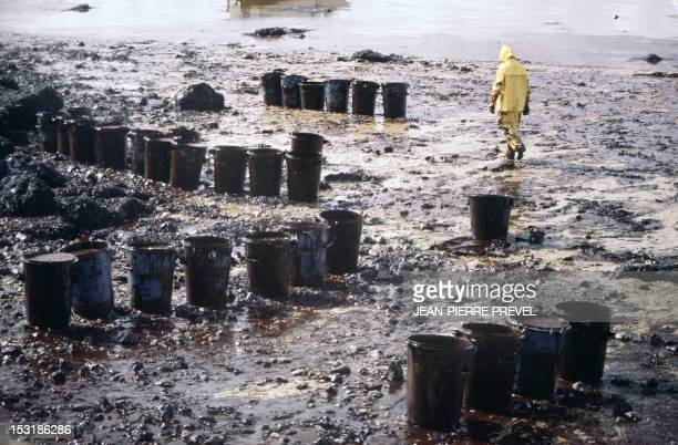 A man walks near garbage cans filled with oil in April 1978 during the cleaning up of a beach covered with oil after the sinking of the oil tanker...