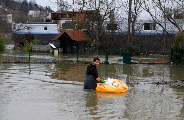 A Man Walks Near His Houseboat On The Banks Of The Flooded Seine