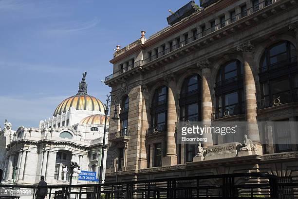 A man walks near Mexico's central bank headquarters the Banco de Mexico right and the Palacio de Bellas Artes left in Mexico City Mexico on Tuesday...
