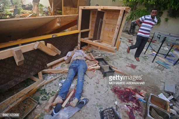 A man walks near the body of a person killed in an attack at the Pizza House restaurant in Mogadishu on June 15 2017 A suicide car bombing and...