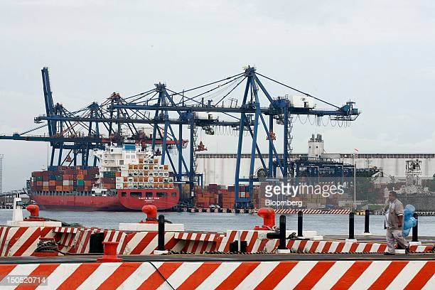 A man walks near the harbor as a cargo ship filled with containers arrives to be unloaded at the Port of Veracruz Mexico on Friday Aug 17 2012...