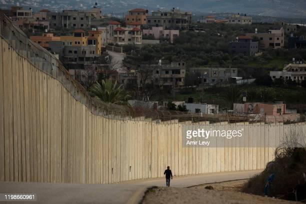 Man walks near the Israeli West Bank barrier in the Israeli-Arab town of Baqa Al-Gharbiyye as the Palestinian village Naslat Isa is seen on the other...