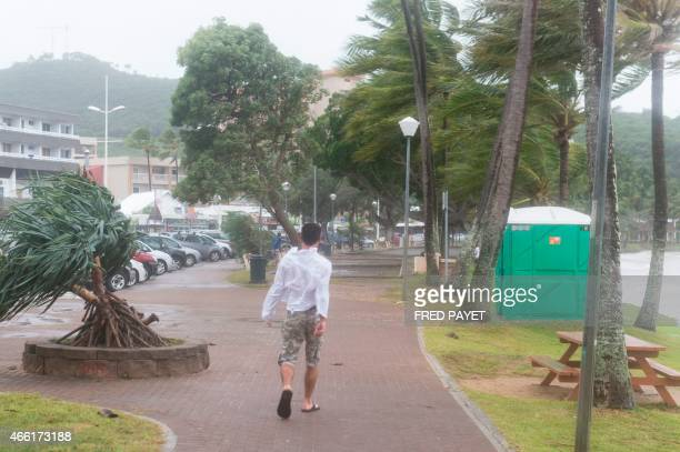 A man walks near the sea on March 14 2015 in Anse Vata south of Noumea New Caledonia Rain and wind were observed in the island but the Tropical...