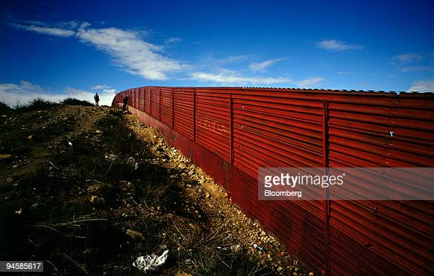 A man walks near the US/Mexico border fence as seen from the Mexican side at Las Playas in the city of Tijuana Mexico on Jan 30 2007