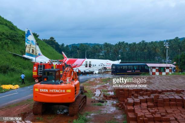 Man walks near the wreckage of an Air India Express jet at Calicut International Airport in Karipur, Kerala, on August 8, 2020. - Fierce rain and...