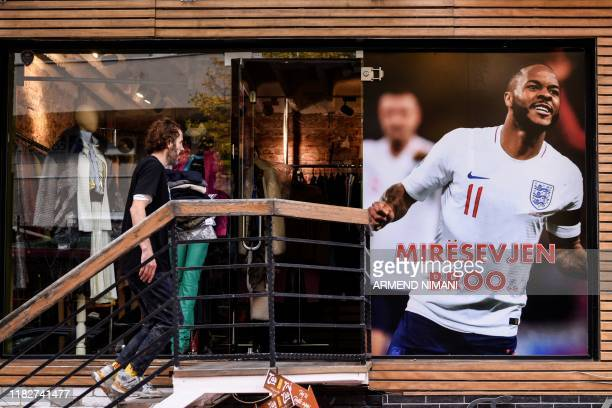 A man walks next to a banner picturing England's forward Raheem Sterling and reading Welcome Bro displayed on the facade of a clothing store in...