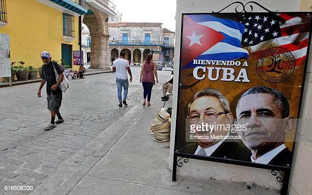 Man walks next to a banner with the faces of Barack Obama and Raul Castro as Cuba prepares for the visit of U.S. President Barack Obama on March 19,...