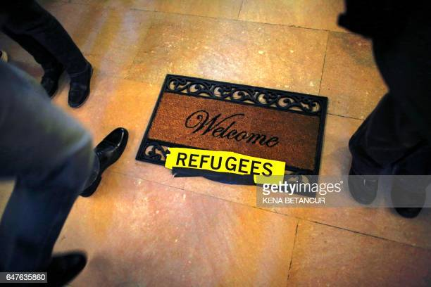 TOPSHOT A man walks next to a carpet that said Welcome Refugees during a protest called 'No Ban No Wall Get Loud' hosted by Amnesty International USA...