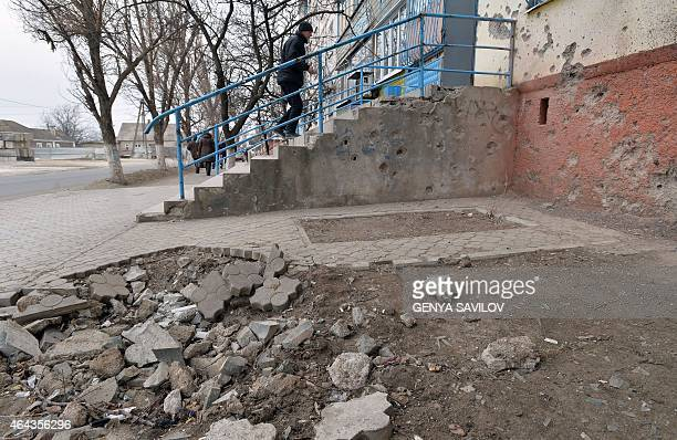 Man walks next to a damaged sidewalk into a building damaged after shelling in the southeastern Ukrainian city of Mariupol, Donetsk region, on...