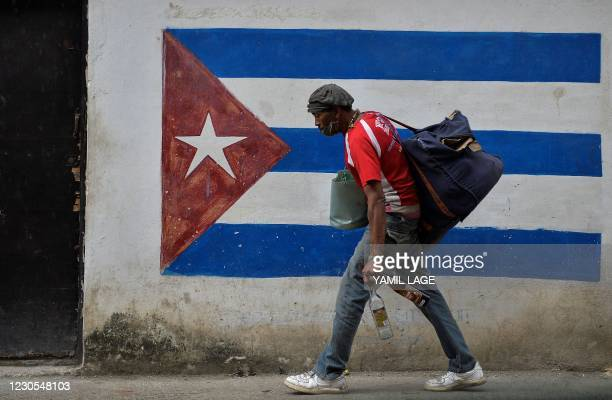 Man walks next to a graffiti of the Cuban flag in Havana, on January 12, 2021. - Cuba's foreign affairs minister Bruno Rodriguez on Monday slammed...