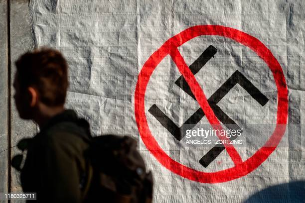 A man walks next to a logo of Nazi swastika during an antifascist rally outside the Court of Appeal during the testify of former MP and leader of...