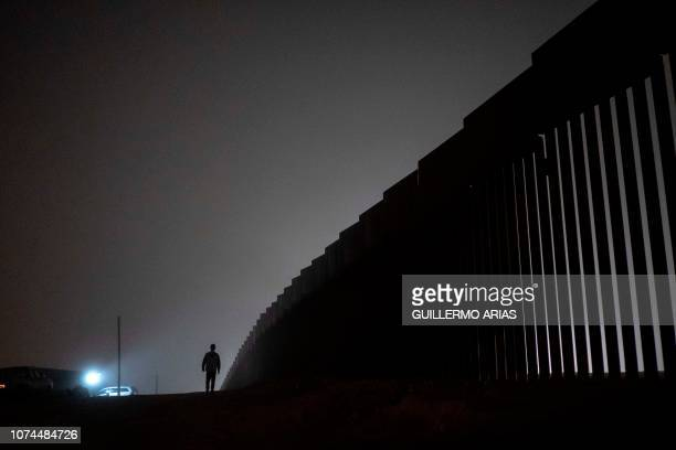 A man walks next to a reinforced section of the USMexico border fence is seen from Tijuana Baja California state Mexico on December 20 2018 Donald...