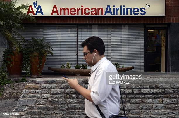 A man walks next to an American Airlines ticket sale office in Caracas on June 17 2014 American Airlines announced earlier today that it will cut...