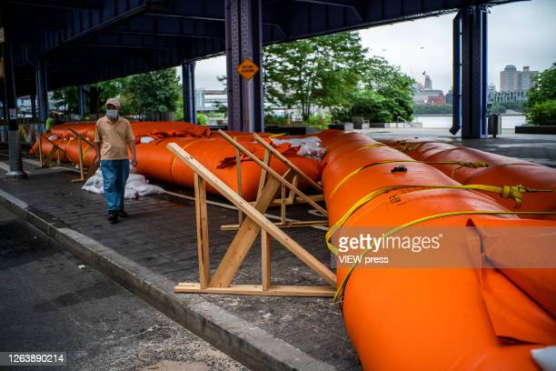 A man walks next to flood barriers used to prevent flooding at the South Street Seaport as the city gets ready for tropical storm Isaias on August 4...