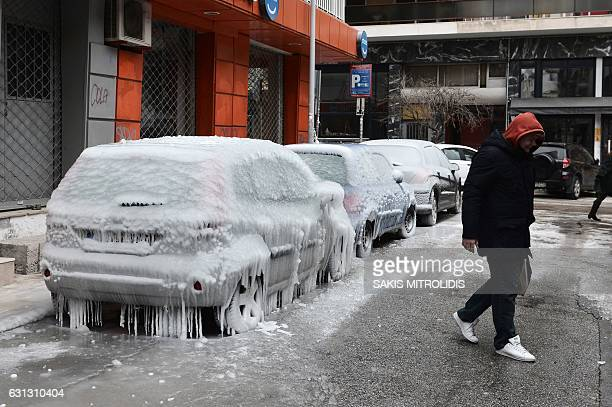 A man walks next to frozen cars in Thessaloniki on January 9 2017 The icy conditions left many households in the Thessaloniki region without water as...