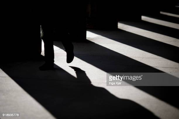 A man walks next to pillars that throw a shadow on February 14 2018 in Berlin Germany