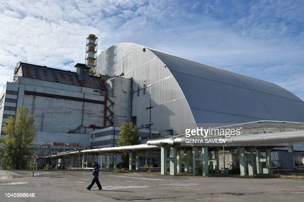A man walks next to the New Safe Confinement over the fourth block of the Chernobyl nuclear plant in Chernobyl on October 5 2018 Ukraine has launched...